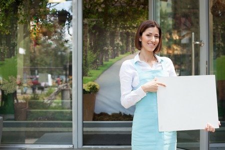 a placard: Cheerful saleswoman is standing near her flower shop. She is holding an empty white billboard and pointing her finger at it. The woman is looking forward and smiling. Copy space in left side