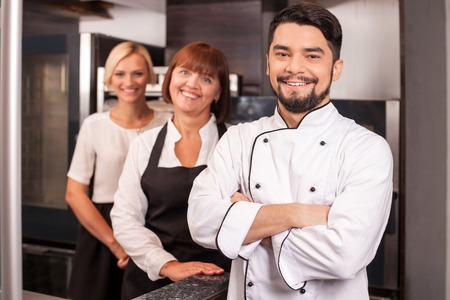 Attractive young male baker and his assistants are standing in kitchen. They are smiling happily. The cooking team is looking at the camera happily