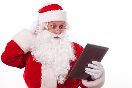 he old: Old Father Christmas is holding a laptop and looking at with shock. He does not know what it is. The man is touching his head pensively. Isolated on background