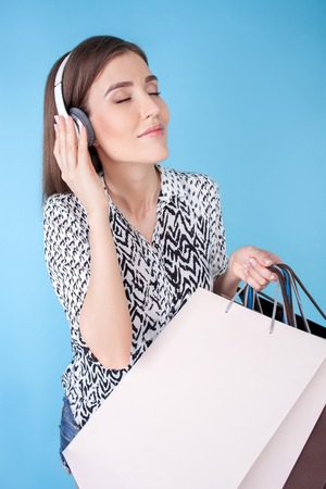 boastful: Cheerful woman is standing and holding packets of bought clothing. She is listening to music from earphones and smiling. The lady closed her eyes with enjoyment. Isolated on blue background