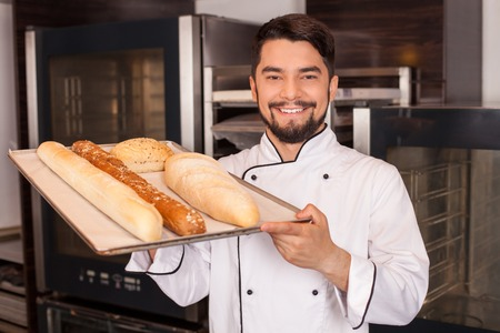 Handsome chef is standing in bakery and smiling. He is holding a tray with baked products and showing it to camera proudly