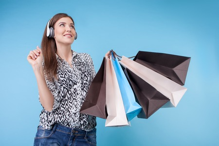 boastful: Attractive styled girl is going shopping with joy. She is listening to music from headphones and smiling. The lady is holding packets and looking up dreamingly. Isolated on blue background