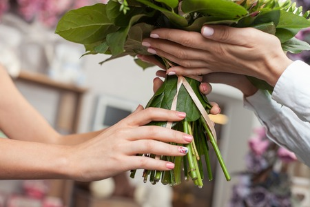 selling service: Close up of hands of successful florist giving a bouquet to her customer