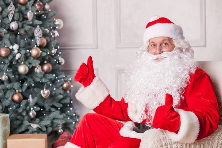 christmas santa: Old Father Christmas is giving thumbs up with both his hands. He is sitting in his chair near a Christmas tree and smiling. The man is looking forward happily