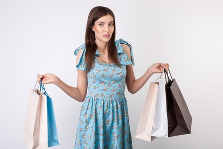 things to do: Beautiful woman is standing and holding a lot of packets. She does not know what to do with so many bought things. The lady is shrugging with doubt. Isolated on background Stock Photo