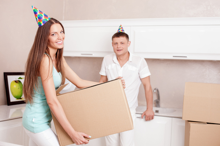 move in: Beautiful husband and wife are packing their staff for move in another building. They are wearing holiday caps and smiling. The woman is holding a box with happiness Stock Photo