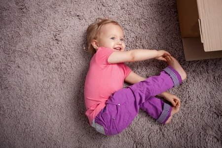 carpet flooring: Cute small girl is relaxing on flooring with joy. She is lying on carpet near boxes. The kid is touching her thumbs with her arms and smiling. Copy space in left side