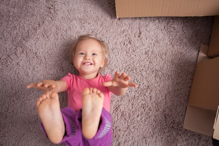 carpet and flooring: Pretty small girl is lying on flooring with joy. She is stretching her hands and legs up and smiling. There are cardboard boxes near her