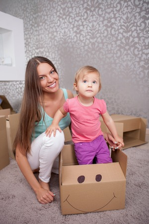common room: Attractive mother with her little daughter are moving in another apartment. The girl is standing in cardboard box and looking forward with interest. Her mother is kneeing near her and smiling