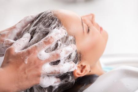 La muchacha atractiva está consiguiendo un Champú de peluquería. Ella se está inclinando su cabeza sobre el fregadero y relajante. Sus ojos se cierran con el disfrute. La peluquería está lavando el cabello con champú