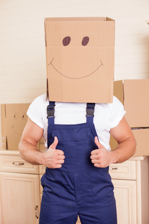 moving box: Cute man is standing in an apron. He is holding a cardboard box on his head. The man is giving thumbs with joy. He is moving in another apartment