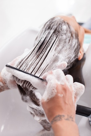 foamed: Cheerful girl is having her hair washed in beauty shop. She closed her eyes with enjoyment. The hairdresser is combing her foamed hair gently Stock Photo