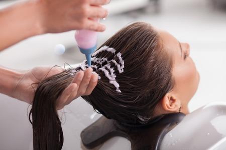 champú: Hermosa mujer tiene el pelo se lava en salón de belleza. Ella está sentada con alegría y relajante. La peluquería está sosteniendo una botella de champú y aplicarlo sobre el cabello del cliente Foto de archivo