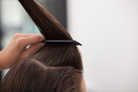 combing hair: Close up of arms of professional hairdresser holding a com and a bunch of female hair. She is combing hair of woman. Copy space in right side