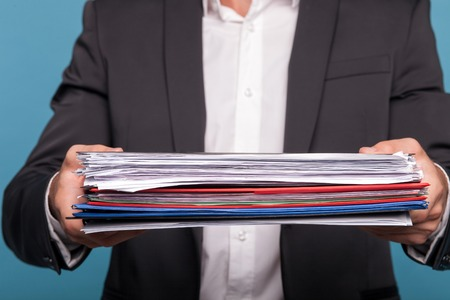 personal finance: Close up of body of businessman holding a heap of documents in his arms