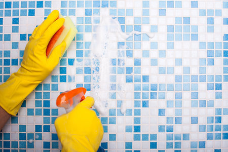 houseman: Close up of male hands washing tile in bathroom. The cleaner is spraying the wall and scrubbing it with a washcloth. The man is wearing gloves. Copy space in right side Stock Photo