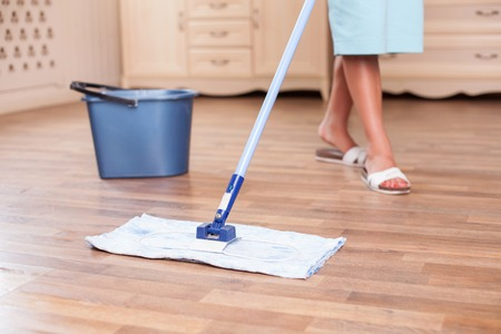 Close up of legs of female cleaner mopping flooring. The woman is standing near a bucket