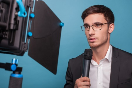 Attractive reporter is holding a microphone and telling news. The man is looking at the camera seriously. He is wearing suit and eyeglasses. Isolated on blue background Stock Photo