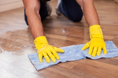 washcloth: Close up of male hands holding a washcloth and washing flooring. The man is kneeing. He is wearing yellow gloves