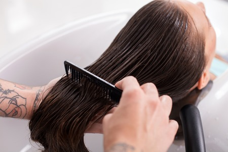 Close up of arms of hairstylist combing female hair with balsam. The woman is leaning her head on the sink and relaxing. Her eyes are closed with enjoyment Stock Photo