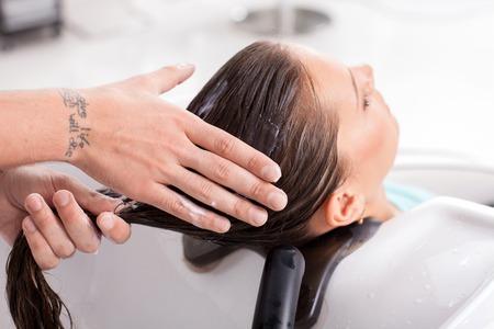 mujer limpiando: Cerca de las manos masculinas de peluquería aplicar bálsamo de cabello en la mujer. La mujer está sentada y relajante. Cerró los ojos con placer
