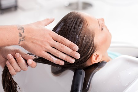woman washing hair: Close up of male hands of hairdresser applying balsam on female hair. The woman is sitting and relaxing. She closed her eyes with pleasure