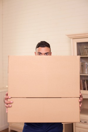 cardboard only: Cheerful man is standing and holding cardboard boxes. His eyes are only visible. The man is looking forward with interest