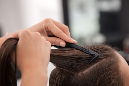 combing: Close up of hands of skilled hairstylist combing female wet hair