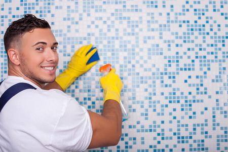 servicio domestico: Lavadora masculino hermoso es la limpieza de la superficie de azulejos en el ba�o. El hombre es la celebraci�n de un spray de limpieza y una esponja en la mano. �l est� de pie y sonriente. Copiar espacio en el lado derecho Foto de archivo
