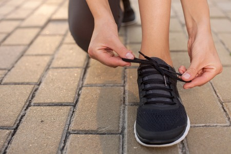 lacing sneakers: Close up of legs of sport girl lacing her sneakers. The woman is kneeing on the footpath in park