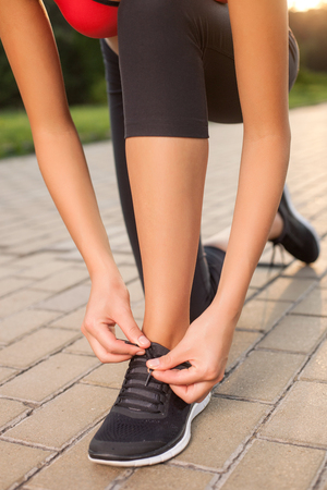 lacing sneakers: Close up of body of sportswoman kneeing on the road in park. The woman is lacing up her sneakers. The girl is ready for running