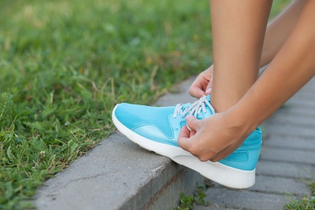 lacing sneakers: Close up of legs of sport girl lacing up her blue sneakers before jogging. The athlete is standing on footpath in park and leaning her leg on the border
