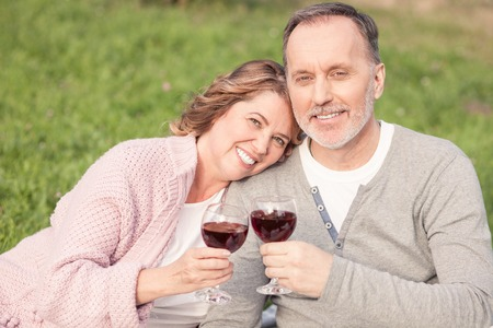 wife: Pretty mature husband and wife are celebrating their anniversary. They are sitting on grass and drinking wine. The man and woman are looking at the camera and smiling