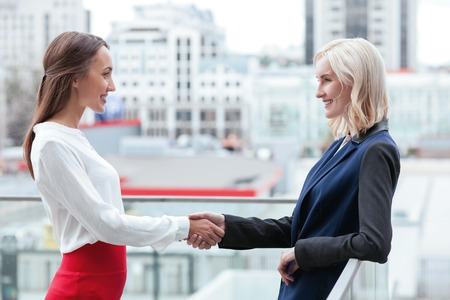 formalwear: Beautiful female business partners made a deal. They are shaking hands and smiling. The women are standing outdoors in formalwear Stock Photo