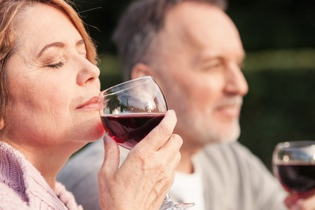 woman laying: Cute mature husband and wife are drinking wine with joy. They are sitting on grass and smiling. The woman is smelling red drink. She closed her eyes with enjoyment