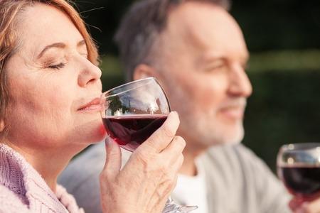 mujer enamorada: Marido maduros lindos y mujer están bebiendo vino con alegría. Están sentados en el césped y sonriendo. La mujer está oliendo bebida roja. Cerró los ojos con el disfrute Foto de archivo