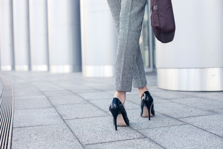 heel: Close up of female legs of worker standing near her office. The woman is wearing formalwear and shoes on high heels. She is holding a handbag. Copy space in left side