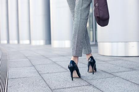 chaussure: Gros plan des jambes f�minines de travailleurs debout pr�s de son bureau. La femme porte formalwear et des chaussures sur des hauts talons. Elle tient un sac � main. espace de copie dans le c�t� gauche Banque d'images
