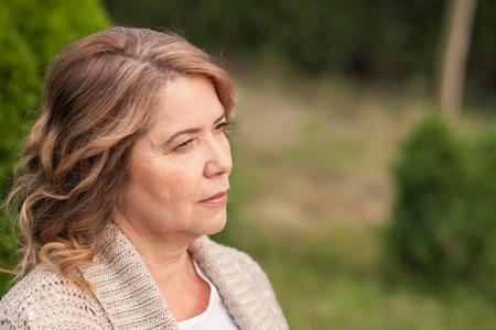 mujeres maduras: Bastante vieja mujer está de pie y descansando en el parque. Ella está soñando y mirando a un lado pensativo. Copiar espacio en el lado derecho