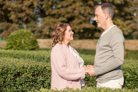 manos entrelazadas: Marido madura alegre y mujer están de pie y descansando en el parque. Están tomados de la mano y mirando el uno al otro feliz. Los amantes están sonriendo. Copiar espacio en el lado izquierdo