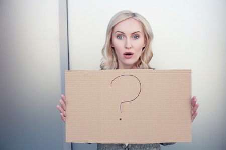 Beautiful young businesswoman is holding a signboard with a question mark on it. She is looking at the camera with frustration. Her mouth and eyes are wide open Stock Photo
