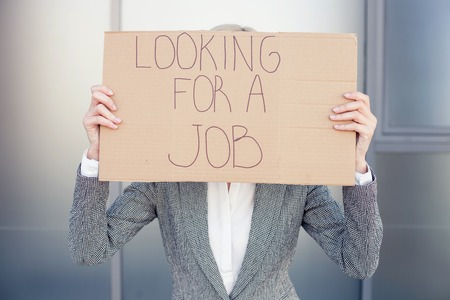 workless: Pretty woman in formalwear is looking for a job. She is standing and holding a cardboard signboard. The lady is covering her face with it