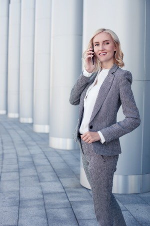 femme blonde: Beautiful businesswoman is talking on the telephone with her business partner. She is standing outdoors and smiling. The lady is looking aside with joy Banque d'images