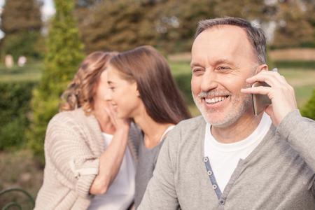 hablando por celular: Alegre viejo matrimonio y su hija están sentados en el banco al aire libre. Ellos son relajantes y sonriente. El hombre está hablando por teléfono con alegría. La madre y la hija están chismeando