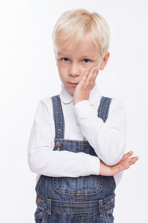 listless: Pretty male child is bored. He is looking at the camera with sadness. The schoolboy is standing and touching his cheek. Isolated on background Stock Photo
