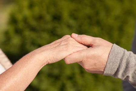 woman hands up: Close up of arms of mature married couple. They are holding hands with love. The man and woman are standing in park