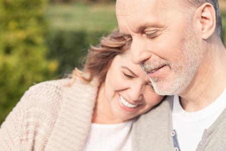 꽤 성숙한 남편과 아내가 공원에 서서 포용하고 있습니다. 그들은 웃고있다.