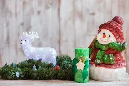 pine wreath: Happy New Year. Holiday toy snowman, candle and bear are situated near pine wreath Stock Photo