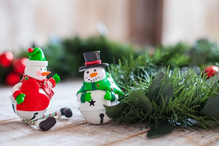 snowman wood: Marry Christmas. Cheerful two toy snowmen are standing on white wood surface near pine garland