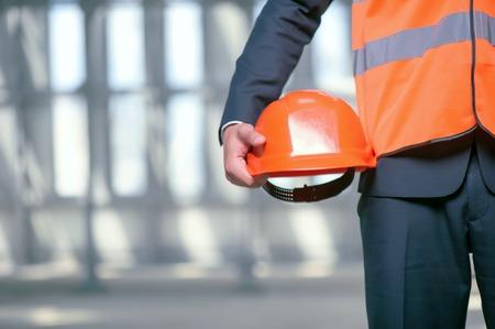 seguridad en el trabajo: Cierre de constructor irreconocible pie y la celebraci�n de un casco de color naranja en la mano. El hombre lleva una ropa de trabajo. Copiar espacio en el lado izquierdo